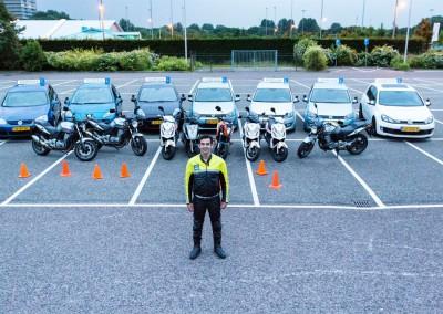 Adrian in het midden met op de achtergrond de voertuigen die gebruikt worden bij het geven van les.